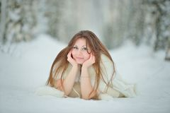 Winter woman portrait lying on the snow Royalty Free Stock Images