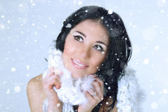 Winter woman portrait in white knitted scarf on snowflakes background. Stock Image