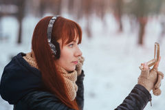 Winter. Woman with red hair looking in the mirror on the street. Female wearing ear muffs does make-up Stock Photo