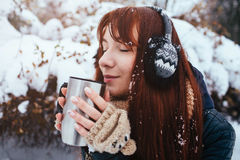Winter. Woman with red hair wearing ear muffs. Girl drinking hot tea or coffee  iron insulated cup Stock Image
