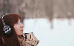 Winter. Woman with red hair wearing ear muffs. Girl drinking hot tea or coffee  iron insulated cup Royalty Free Stock Photography