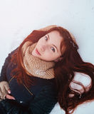 Winter. Woman with red hair wearing ear muffs looking at the camera Stock Photography