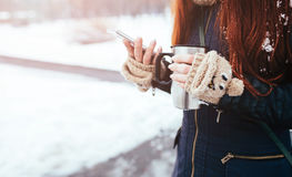 Winter. Woman with red hair wearing gloves . Girl drinking hot tea or coffee  iron insulated cup. It uses a phon Royalty Free Stock Photos