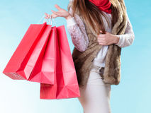 Winter woman with red paper shopping bags. Winter woman in warm clothes with red paper shopping bags on blue. Girl buying. Sale and retail Royalty Free Stock Images