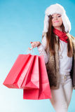 Winter woman with red paper shopping bags. Winter woman in warm clothes fur cap with red paper shopping bags on blue. Girl buying. Sale and retail Stock Photo
