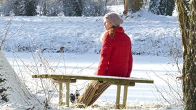 Winter. A woman sitting on a park bench in winter stock footage