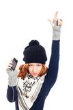 Winter woman with smartphone pointing up Royalty Free Stock Image