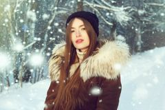 Winter woman in snow looking at camera outside on snowing cold winter day. Portrait Caucasian female model outside in first snow royalty free stock images