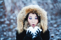 Winter woman in snow outside on snowing cold winter day. Royalty Free Stock Photography