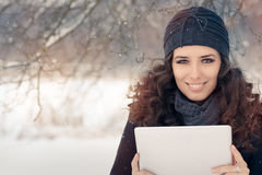 Winter Woman with Tablet Outside in the Snow. Beautiful smiling woman in wintertime decor holding a PC tablet Stock Photo