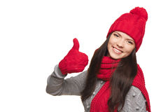 Winter woman thumb up. Closeup of happy woman wearing red warm winter hat, scarf and gloves gesturing thumb up, over white background Royalty Free Stock Photography