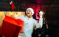 Winter woman wearing red santa claus hat. Woman smile christmas. Euphoria. Happy people. Cute young woman with santa hat. Celebration. Home Christmas royalty free stock image