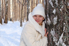Winter woman. Woman in a white coat in winter birch forest leaning on a  birch tree Stock Photos