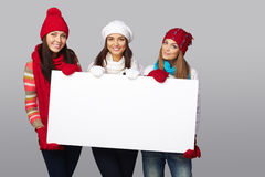 Winter women billboard sign. Women billboard sign. Three young beautiful women wearing winter clothing smiling showing blank white placard. Casual and relaxed Stock Images