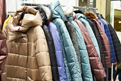 Winter women`s jackets on hanger in store Royalty Free Stock Photos