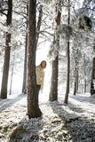 Winter wonderland. Young beautiful woman standing and peeking out behind pine tree in frost covered forest during sunset Stock Photo
