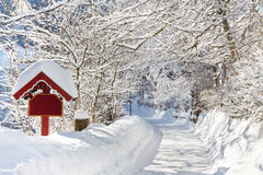 Winter Wonderland. A beautiful day in winter wonderland. Snowcapped trees over snowy country road Stock Photo
