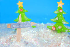 Winter wonderland. Ceramic decorative christmas ornaments in a field of snow with christmas tree, fence and a winter wonderland sign royalty free stock photo