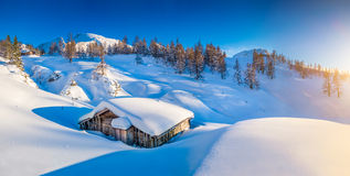 Winter wonderland in the Alps with traditional mountain hut at sunset Royalty Free Stock Photo