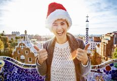 Tourist woman in Santa hat at Guell Park showing thumbs up Stock Photo