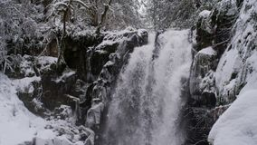 Winter wonderland with cascading waterfall stock video