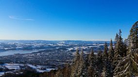 Winter wonderland in Hedmark county Norway. View over Brumunddal from høsbjørg. Nice fir trees and blue sky stock photography