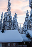 Winter wonderland lapland scene sunset above cabins Royalty Free Stock Image
