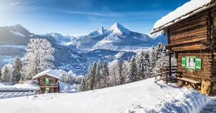 Winter wonderland with mountain chalets in the Alps. Panoramic view of beautiful winter wonderland mountain scenery in the Alps with traditional mountain chalets Royalty Free Stock Photography