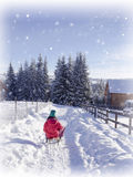 Winter wonderland snow. Girl on sledge Royalty Free Stock Photography