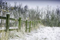 Winter wonderland, Uk. Meadow with green wooden fence on british countryside covered with snow on beautiful winter day.Bare trees in background.Winter stock photos