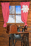 Winter. A wooden house. Window with red curtains. And an old iron sewing machine Royalty Free Stock Photos