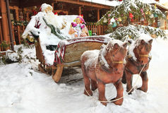 Winter wooden sculpture. Christmas image of snow-covered park with wooden sculpture of  horse-drawn vehicle and Santa Clause Stock Image