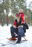 Winter in the woods dad holding his son on his shoulders. Winter in the woods dad holding his son on his shoulders, and he sits on a sled in the snow royalty free stock image