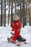 Winter in the woods stands a boy on snow scooter and smiling. Stock Photo