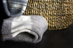 Winter Wool Socks. Wool handmade knitted winter socks laid on the table, a wicker basket in the blurry background Stock Photography
