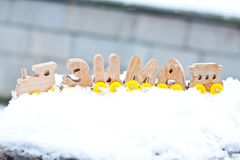 Winter word composed of Russian language wooden letters train cars on the white snow. holiday decorations. Winter word composed of Russian language wooden royalty free stock image
