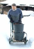 Winter work. An old man carrying a cart buckets of coal in the snow winter environment Royalty Free Stock Images