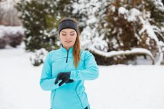 Winter workout. Girl wearing sportswear, looking at watch. Girl wearing sportswear and looking at watch. Winter sports, outdoor fitness, fashion, workout, health Royalty Free Stock Photo