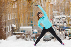 Winter workout. Girl wearing sportswear, stretching exercises. Girl wearing sportswear and doing stretching exercises on snow with urban background. Winter Stock Photography