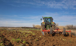 Winter works. Farm tractor preparing the soil Royalty Free Stock Images