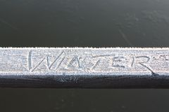 Winter written in frost on a wooden rail. Stock Images