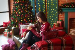 Winter, xmas portrait: Young woman dressed in red warm woolen cardigan posing indoor near Christmas tree royalty free stock photo