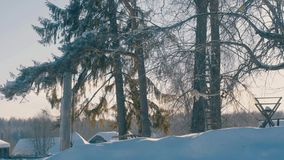 Winter yard in a hoarfrost. Snowfall. Snow covered roofs of wooden houses. 4K stock footage