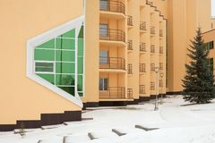 Winter. The yellow facade of the building. Grows a big tree. Royalty Free Stock Images
