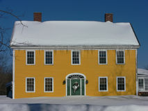 Winter: yellow house in snow. New England yellow house with green door and Christmas wreath in snow Royalty Free Stock Photo