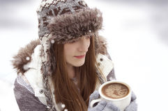 Winter young girl with cup of hot chocolate. Beautiful, young happy woman smiling in a winter setting holding a hot beverage outdoor royalty free stock photos