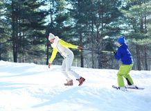 Winter young smiling mother playing with son child go skiing stock image
