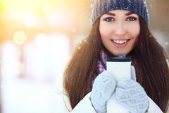 Winter young woman portrait. Beauty Joyful Model Girl holding thermocup with hot tea and smiling, having fun in winter Royalty Free Stock Photo