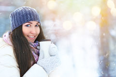 Winter young woman portrait. Beauty Joyful Model Girl holding thermocup with hot tea and smiling, having fun in winter Royalty Free Stock Photography