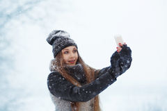 Winter young woman portrait. Beauty Joyful Model Girl laughing and having fun with mobilephone. Beautiful young woman. Outdoors. Enjoying nature, wintertime Stock Photos